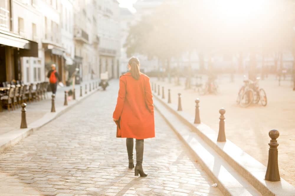 woman wearing red trench coat and leather boots in the street of paris