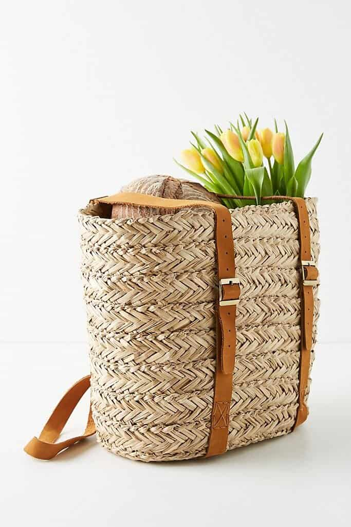 market basket with leather straps and flowers in it
