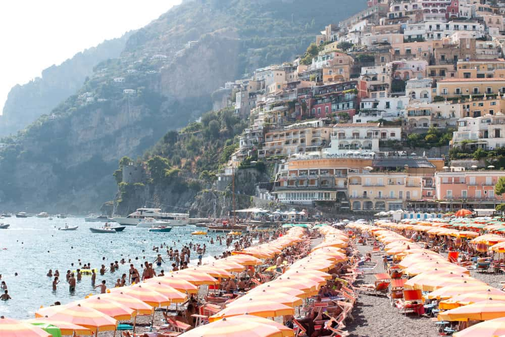 shore at the beach with beach umbrellas and sharing what I am Packing for Italy