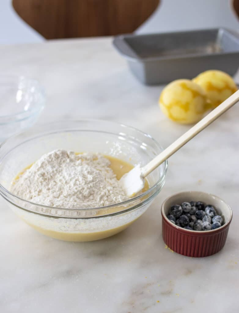 flour in a mixing bowl and blueberries