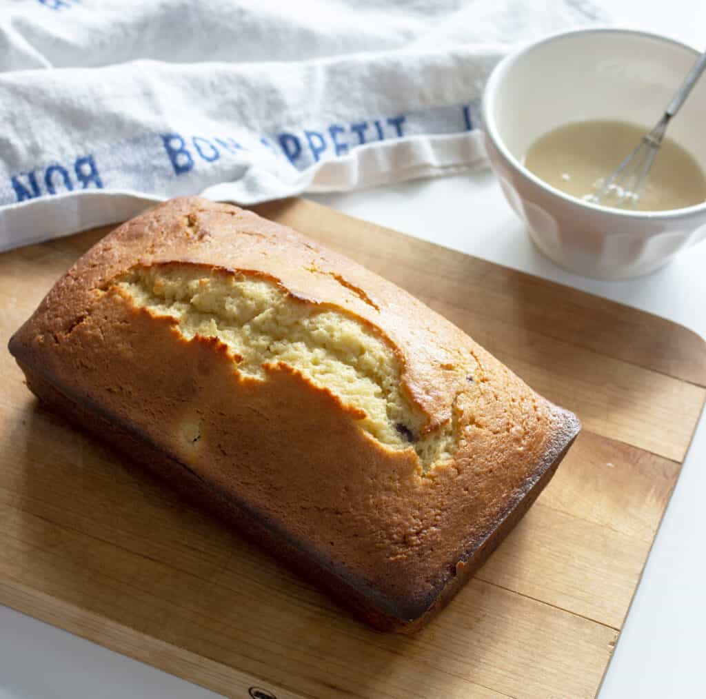 lemon yogurt cake in a slicing board with white bowl and cloth