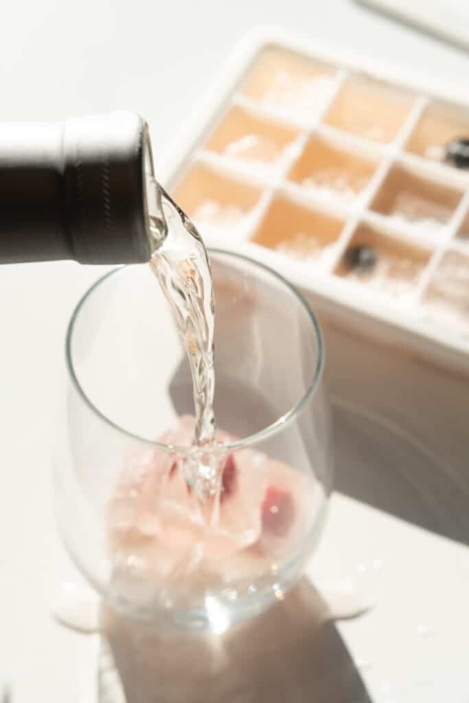 person pouring wine in a glass with Rosé Iced Cubes