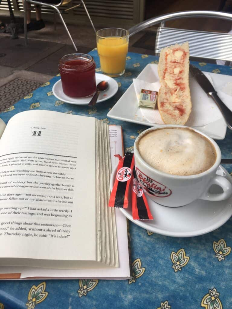 an open book, coffee, jam and bread on a table